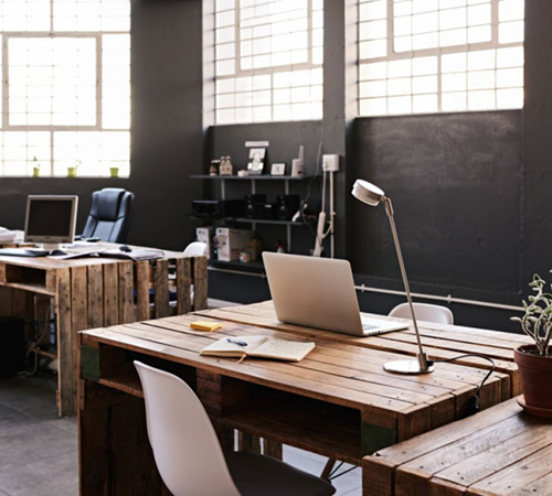 modern office workspace with pallet desks and laptops